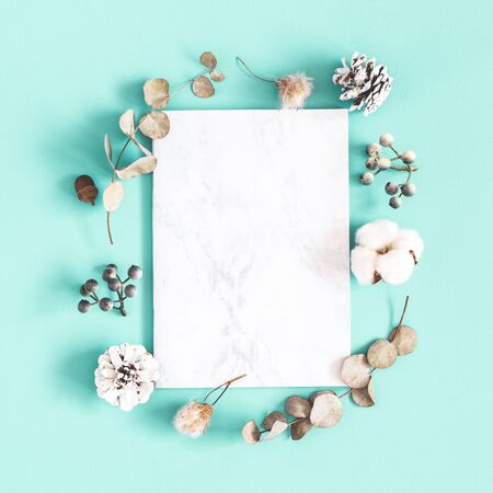 Winter composition. Dried leaves, cotton flowers, berries, pine cones on mint background. Christmas, winter concept. Flat lay, top view, copy space Zdjęcie Seryjne