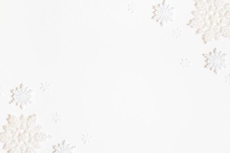 Christmas composition. Frame made of white snowflakes on white background. Christmas, winter, new year concept. Flat lay, top view, copy space Zdjęcie Seryjne