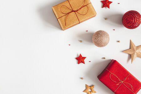 Kerst compositie. Geschenken, rode en gouden versieringen op grijze achtergrond. Kerstmis, winter, nieuwjaarsconcept. Platliggend, bovenaanzicht, kopieerruimte