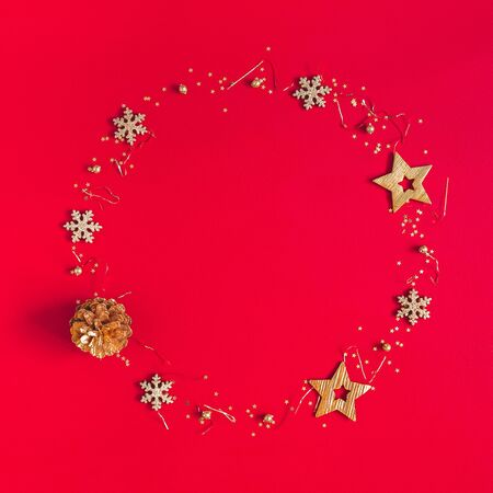 Christmas composition. Wreath made of golden decorations on red background. Christmas, winter, new year concept. Flat lay, top view, copy space