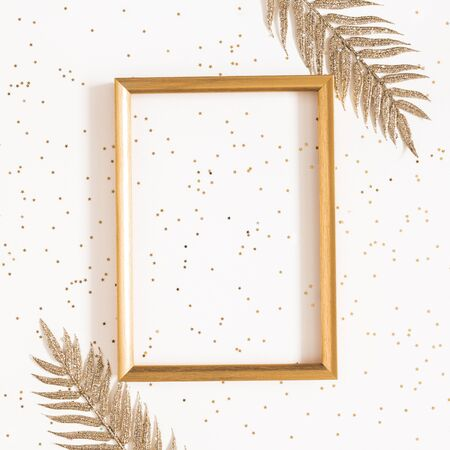Christmas composition. Golden decorations, photo frame on blue background. Christmas, winter, new year concept. Flat lay, top view, copy space