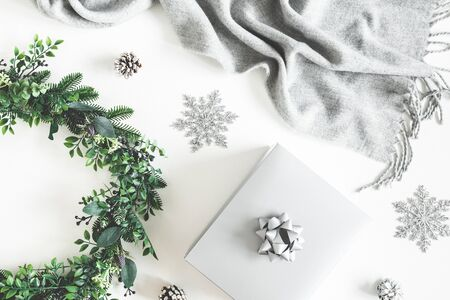 Christmas composition. Gift box, wreath, silver decorations, plaid on white background. Christmas, winter, new year concept. Flat lay, top view, copy space Zdjęcie Seryjne