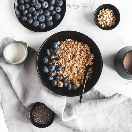 Breakfast with muesli, blueberry, coffee on white background. Healthy food concept. Flat lay, top view