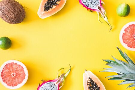 Summer fruits. Tropical fruits on yellow background. Summer concept. Flat lay, top view, copy space