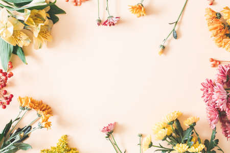Autumn composition. Frame made of fresh flowers on pastel beige background. Autumn, fall concept. Flat lay, top view Stock fotó
