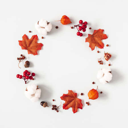 Autumn composition. Wreath made of flowers, maple leaves on gray background. Autumn, fall, thanksgiving day concept. Flat lay, top view
