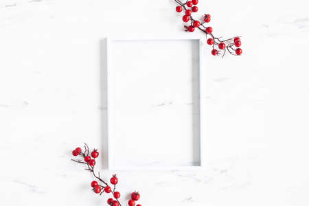 Christmas composition. Red berries, photo frame on marble background. Christmas, winter, new year concept. Flat lay, top view