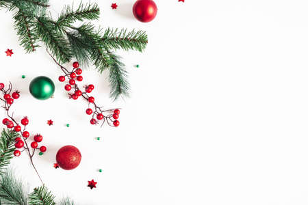 Christmas composition. Fir tree branches, red and green decorations on white background. Christmas, winter, new year concept. Flat lay, top view, copy space