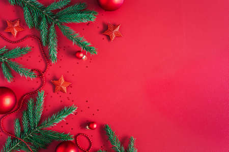 Christmas composition. Christmas red decorations, fir tree branches on red background. Flat lay, top view, copy space Stock fotó