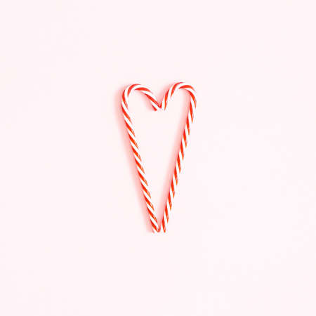 Christmas composition. Heart made of candy canes on pink background. Christmas concept. Flat lay, top view, square Stock fotó