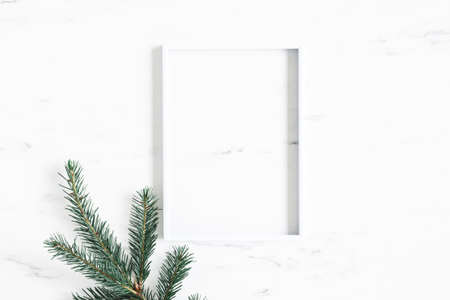 Christmas composition. Fir tree branch, photo frame on marble background. Christmas, winter, new year concept. Flat lay, top view