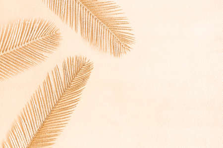 Golden palm leaves on beige background. Flat lay, top view