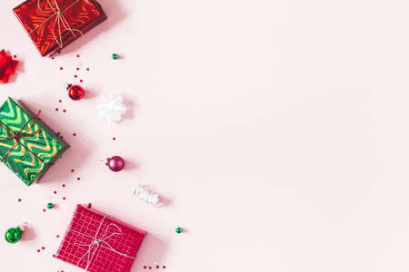Christmas composition. Christmas gifts, decorations on pastel pink background. Flat lay, top view, copy space