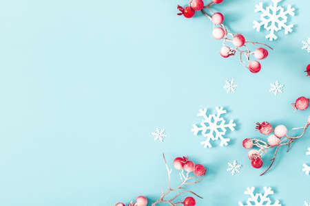 Christmas or winter composition. Snowflakes and red berries on blue background. Christmas, winter, new year concept. Flat lay, top view Stock fotó