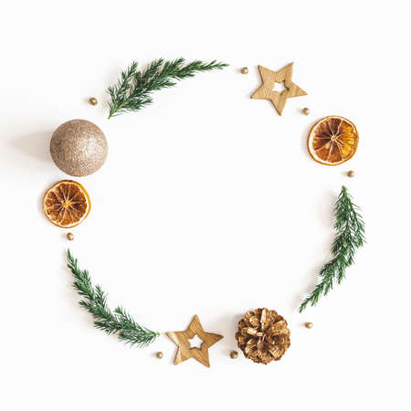 Christmas composition. Wreath made of fir tree branches, golden decorations on white background. Christmas, winter, new year concept. Flat lay, top view