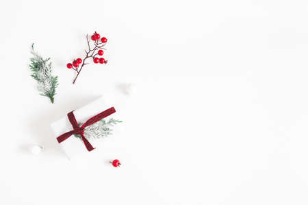 Christmas composition. Frame made of gift, snowflakes, fir tree branches and red berries on white background. Christmas, winter, new year concept. Flat lay, top view
