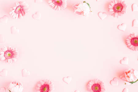 Valentine's Day background. Pink flowers, hearts on pastel pink background. Valentines day concept. Flat lay, top view, copy space 写真素材