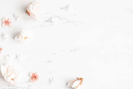 Flowers composition. White and pink flowers on marble background. Flat lay, top view