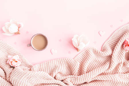 Valentine's Day background. Pink flowers, plaid, cup of coffee on pink background. Valentines day concept. Flat lay, top view, copy space