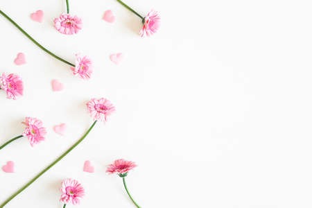 Valentine's Day background. Pink flowers, hearts on white background. Valentines day concept. Flat lay, top view, copy space 写真素材