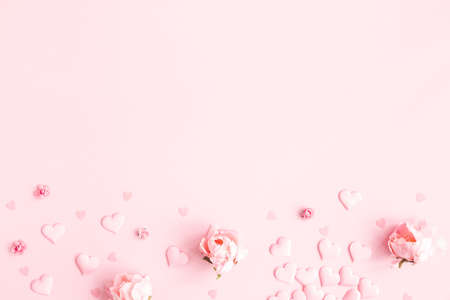 Valentine's Day background. Frame made of pink flowers, hearts on pastel pink background. Valentines day concept. Flat lay, top view, copy space 写真素材