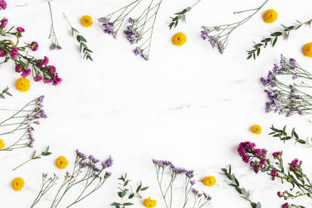 Flowers composition. Colorful flowers and eucalyptus leaves on marble background. Flat lay, top view