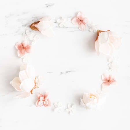 Flowers composition. Wreath made of white and pink flowers on marble background. Flat lay, top view 写真素材