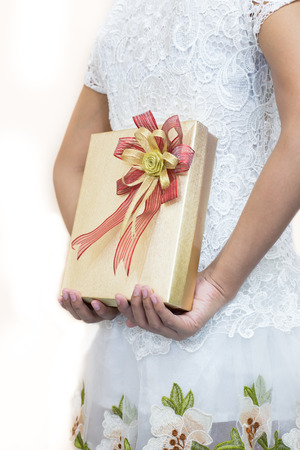gift behind back: Women in white hiding a gift behind her back. Stock Photo