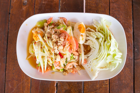 somtum: Green papaya salad with salted egg on wood table. Original spicy thai food is the most popular
