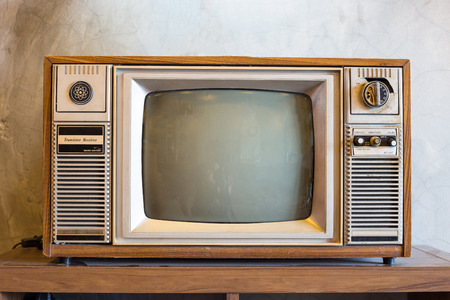 retro tv met houten kast in de kamer met vintage behang op houten tafel