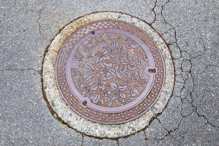 crack pipe: Drain cap art on the surface of sewer cover on the walk way takayama japan Stock Photo