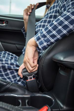 cinturón de seguridad: Primer de la mano de la mujer la fijación de un cinturón de seguridad en el coche