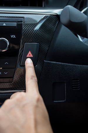 control panel lights: Closeup of young woman pressing emergency button on car sport dashboard. Stock Photo