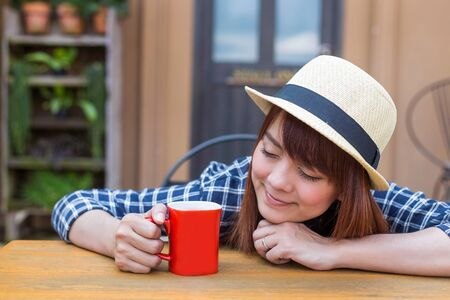 wear hat woman sitting in outdoor with warm drink relax