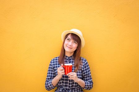 Frau tragen in Kleid und Hut lächelnd roten Kaffeetasse auf gelbem Betonwand Hintergrund, Denken, Phantasie