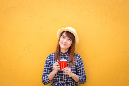 smiling woman wear in dress and hat holding red coffee cup on yellow cement wall background, thinking, imagination Stock Photo