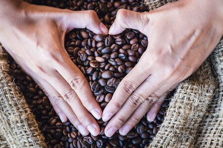 gunny bag: closeup coffee beans in hands of heart shaped with sunlight in gunny bag. i love coffee Stock Photo