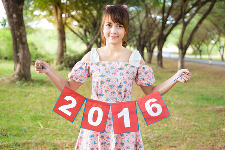 holding paper: smile of cute woman hand holding paper sign 2016, happy new year
