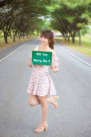 Cute woman hand holding green board sign with text  will you marry meon road and tree, Smiling female model. Stock Photo
