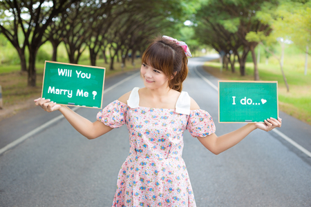 married: Cute woman hand holding green board sign with text  will you marry me and i doon road and tree, Smiling female model. Stock Photo