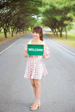 girl dress: Cute woman hand holding green board sign with text  welcome  on road and tree, Smiling female model.