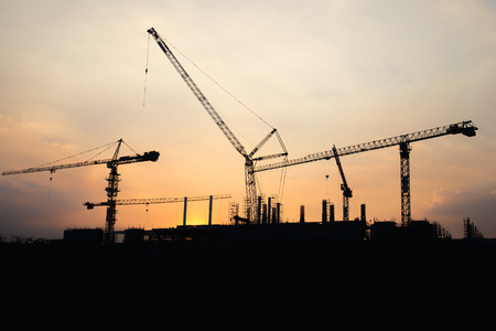 is real: Industrial construction crane working and building at site on sunset time