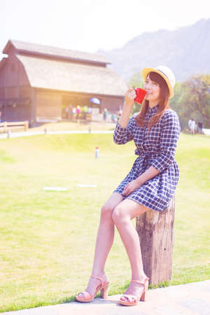 gorgeous girl: wear hat woman sitting in outdoor with warm drink relax pastel color tone Stock Photo