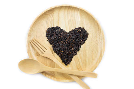 natural pattern: Heart rice berry in wooden bowls with spoon and forkon white background. concept Stock Photo