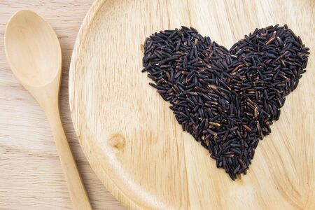 natural pattern: Heart rice berry in wooden bowls with spoon on wooden background. concept