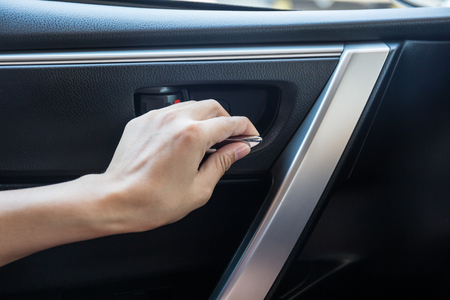 lift lock: Woman driver pressing button locking and unlocking doors in car.