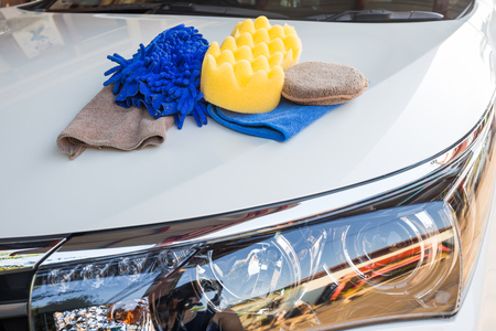 Yellow, green sponges and blue mitts for washing and microfiber fabric with cleaner cloth on white car Stock fotó
