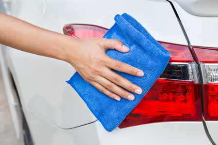 microfiber cloth: Hand with blue microfiber cloth cleaning taillight white car.