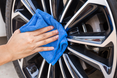rag wheel: Hand with blue microfiber cloth cleaning car wheel.