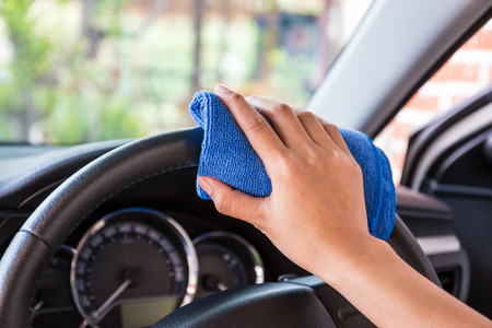 Hand with microfiber cloth cleaning Interior and steering wheel modern car. Stock fotó